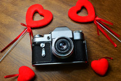 Εκλεκτής ποιότητας κάμερα στον ξύλινο πίνακα με τις κόκκινες καρδιές Στοκ Φωτογραφίες