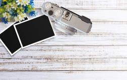 Εκλεκτής ποιότητας κάμερα ταινιών και δύο κενά πλαίσια φωτογραφιών στον ξύλινο πίνακα Στοκ Εικόνα