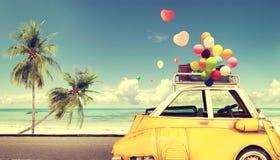 Εκλεκτής ποιότητας κίτρινο αυτοκίνητο με το ζωηρόχρωμο μπαλόνι καρδιών στην παραλία Στοκ Εικόνες