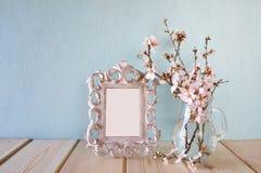 Εκλεκτής ποιότητας κενό πλαίσιο δίπλα στα άσπρα λουλούδια άνοιξη Εκλεκτική εστίαση πρότυπο, έτοιμο να βάλει τη φωτογραφία Στοκ Φωτογραφίες