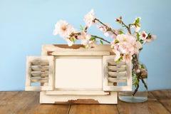 Εκλεκτής ποιότητας κενό πλαίσιο φωτογραφιών δίπλα στα λουλούδια άνοιξη Στοκ Εικόνες