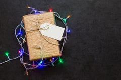 Εκλεκτής ποιότητας κιβώτιο δώρων με τη γιρλάντα Χριστουγέννων στον πίνακα πετρών Στοκ Εικόνα