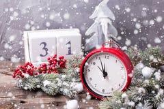 Εκλεκτής ποιότητας κόκκινο ρολόι, ημερολόγιο, δέντρο γουνών κλάδων και κόκκινα μούρα Στοκ Φωτογραφία