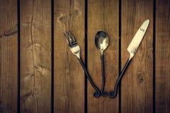 Εκλεκτής ποιότητας μαχαιροπήρουνα - δίκρανο, κουτάλι και μαχαίρι που αερίζονται σε ξύλινο Backgroun Στοκ Φωτογραφίες