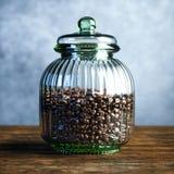 Εκλεκτής ποιότητας μεγάλο βάζο γυαλιού που γεμίζουν με τα φασόλια καφέ στον ξύλινο πίνακα Στοκ εικόνα με δικαίωμα ελεύθερης χρήσης