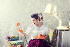 Εκλεκτής ποιότητας νοικοκυρά που φωνάζει στο τηλέφωνο στο σαλόνι Στοκ Εικόνες