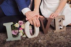 Εκλεκτής ποιότητας ξύλινη αγάπη επιγραφής και χέρια ακριβώς του παντρεμένου ζευγαριού Στοκ Εικόνες