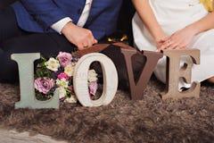 Εκλεκτής ποιότητας ξύλινη αγάπη επιγραφής και χέρια ακριβώς του παντρεμένου ζευγαριού Στοκ Φωτογραφίες