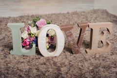 Εκλεκτής ποιότητας ξύλινη αγάπη επιγραφής με τα λουλούδια στο καφετί υπόβαθρο Στοκ Εικόνες