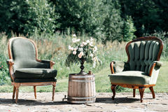 Εκλεκτής ποιότητας ξύλινοι καρέκλες και πίνακας με τη διακόσμηση λουλουδιών στον κήπο υπαίθριος Στοκ Εικόνα