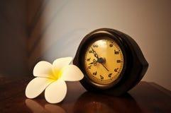 Εκλεκτής ποιότητας ξύλινο ταϊλανδικό ρολόι γραφείων σε έναν πίνακα με το λουλούδι plumeria Στοκ εικόνα με δικαίωμα ελεύθερης χρήσης