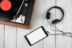 Εκλεκτής ποιότητας περιστροφική πλάκα, smartphone και ακουστικά Στοκ Φωτογραφίες