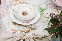 Εκλεκτής ποιότητας πιάτα με τα τριαντάφυλλα σε έναν πίνακα με τα μαχαιροπήρουνα και τα γυαλιά Στοκ εικόνα με δικαίωμα ελεύθερης χρήσης