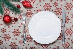 Εκλεκτής ποιότητας πιάτο Χριστουγέννων στο υπόβαθρο διακοπών με τις κόκκινες διακοσμήσεις Χριστουγέννων Στοκ Εικόνες