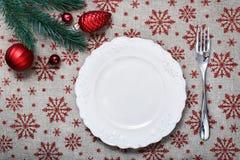 Εκλεκτής ποιότητας πιάτο Χριστουγέννων στο υπόβαθρο διακοπών με τις κόκκινα διακοσμήσεις & x28 Χριστουγέννων κώνοι, balls& x29  Στοκ εικόνα με δικαίωμα ελεύθερης χρήσης