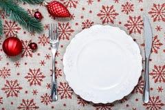 Εκλεκτής ποιότητας πιάτο Χριστουγέννων στο υπόβαθρο διακοπών με τις κόκκινες διακοσμήσεις Χριστουγέννων Το υπόβαθρο καμβά με το κ Στοκ Φωτογραφία