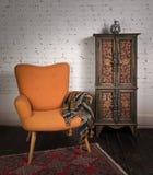 Εκλεκτής ποιότητας πορτοκαλιά πολυθρόνα, διακοσμημένο ντουλάπι, μαύρα μαντίλι και κόκκινο χαλί Στοκ Φωτογραφίες