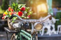 Εκλεκτής ποιότητας ποδήλατο με τα λουλούδια ανθοδεσμών στο καλάθι Στοκ Φωτογραφίες