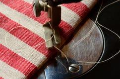 Εκλεκτής ποιότητας ράβοντας μηχανή με το άσπρο νήμα και το ριγωτό ύφασμα Στοκ Εικόνες