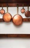 Εκλεκτής ποιότητας τηγάνια χαλκού που κρεμιούνται στο ξύλινο ράφι Στοκ φωτογραφία με δικαίωμα ελεύθερης χρήσης