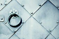 Εκλεκτής ποιότητας υπόβαθρο μετάλλων - παλαιά γκρίζα πόρτα με τα καρφιά και ηλικίας λαβή πορτών μετάλλων υπό μορφή δαχτυλιδιού Στοκ Εικόνα