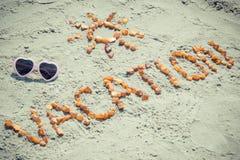 Εκλεκτής ποιότητας φωτογραφία, διακοπές του Word με τη μορφή του ήλιου και γυαλιά ηλίου στην άμμο στην παραλία, θερινός χρόνος Στοκ φωτογραφίες με δικαίωμα ελεύθερης χρήσης