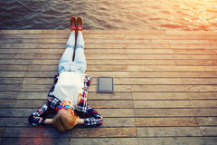 Εκλεκτής ποιότητας φωτογραφία της χαλαρώνοντας νέας γυναίκας στη φύση με την ταμπλέτα Στοκ Εικόνες