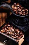 Εκλεκτής ποιότητας χειρωνακτικός μύλος καφέ με τα φασόλια καφέ ξύλινο σε καφετή Στοκ εικόνες με δικαίωμα ελεύθερης χρήσης