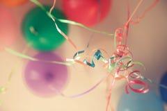Εκλεκτής ποιότητας χρόνια πολλά υπόβαθρο κομμάτων με τις ζωηρόχρωμα δεμένα κορδέλλες και τα μπαλόνια στον μπλε τόνο Στοκ φωτογραφία με δικαίωμα ελεύθερης χρήσης
