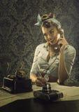 Εκλεκτής ποιότητας ύφος - γυναίκα που μιλά στο τηλέφωνο με το αναδρομικό τηλέφωνο πινάκων Στοκ Φωτογραφία