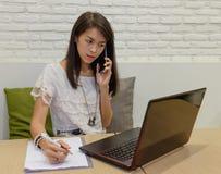 Εκλεκτική εστίαση στις ταϊλανδικές ενήλικες γυναίκες που εργάζονται με το lap-top στο σπίτι Στοκ Εικόνα