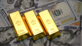 Εκλεκτική εστίαση των χρυσών φραγμών και των δολαρίων σε έναν πίνακα απόθεμα βίντεο