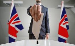 Εκλογή ή δημοψήφισμα στη Μεγάλη Βρετανία Ο ψηφοφόρος κρατά το φάκελο διαθέσιμο επάνω από την ψήφο Ηνωμένες σημαία στο υπόβαθρο Στοκ Φωτογραφία