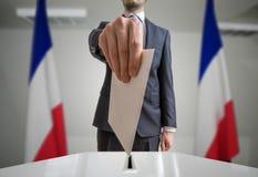 Εκλογή στη Γαλλία Ο ψηφοφόρος κρατά το φάκελο διαθέσιμο επάνω από τη σφαίρα ψηφοφορίας Ευρύς πυροβολισμός γωνίας Στοκ εικόνα με δικαίωμα ελεύθερης χρήσης
