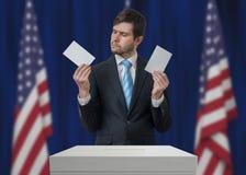 Εκλογή στις Ηνωμένες Πολιτείες της Αμερικής Ο αναποφάσιστος ψηφοφόρος κρατά τους φακέλους επάνω από την ψήφο ψηφοφορίας Στοκ Εικόνα