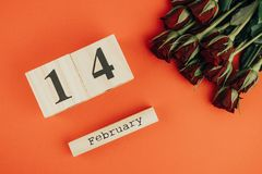 Ελάχιστη έννοια ημέρας βαλεντίνων του ST στο κόκκινο υπόβαθρο Κόκκινα τριαντάφυλλα και ξύλινος caledar με στις 14 Φεβρουαρίου σε  Στοκ φωτογραφία με δικαίωμα ελεύθερης χρήσης