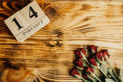 Ελάχιστη έννοια ημέρας βαλεντίνων του ST στο ξύλινο υπόβαθρο Κόκκινα τριαντάφυλλα και ξύλινος caledar με στις 14 Φεβρουαρίου σε τ Στοκ εικόνες με δικαίωμα ελεύθερης χρήσης