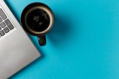 Ελάχιστος χώρος εργασίας με το φλυτζάνι lap-top και καφέ στοκ εικόνες
