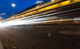 Ελαφριά ίχνη αυτοκινήτων στην οδό κοντά στην οδική γέφυρα, άνθρωποι που περπατούν στη γρήγορη κίνηση, υπόβαθρο οδών νύχτας στοκ εικόνα με δικαίωμα ελεύθερης χρήσης