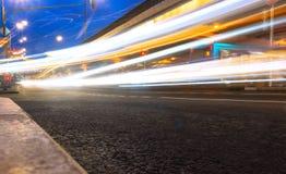 Ελαφριά ίχνη αυτοκινήτων στην οδό κοντά στην οδική γέφυρα, άνθρωποι που περπατούν στη γρήγορη κίνηση, υπόβαθρο οδών νύχτας στοκ φωτογραφία