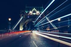 Ελαφριά ίχνη πόλεων της κυκλοφορίας στη γέφυρα Λονδίνο πύργων τη νύχτα Στοκ Εικόνα