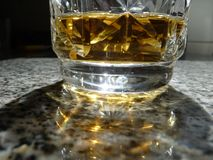 Ελαφριά αντανάκλαση πέρα από ένα ποτήρι του μπέρμπον στοκ φωτογραφία