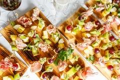 Ελαφριά πρόχειρα φαγητά σε ένα πιάτο σε έναν πίνακα μπουφέδων Ανάμεικτα μίνι καναπεδάκια, λιχουδιές και πρόχειρα φαγητά, τρόφιμα  στοκ εικόνες με δικαίωμα ελεύθερης χρήσης