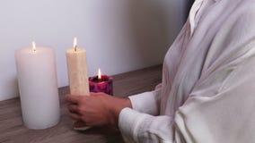 Ελαφριά πυράκτωση κεριών στα χέρια γυναικών ` s απόθεμα βίντεο