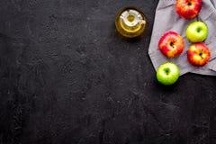 Ελαφριά σάλτσα σαλάτας Ξίδι μηλίτη της Apple στο μπουκάλι μεταξύ των φρέσκων μήλων στο μαύρο διάστημα αντιγράφων άποψης υποβάθρου Στοκ εικόνα με δικαίωμα ελεύθερης χρήσης