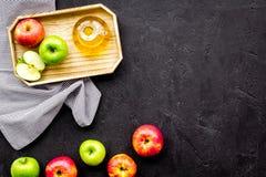 Ελαφριά σάλτσα σαλάτας Ξίδι μηλίτη της Apple στο μπουκάλι μεταξύ των φρέσκων μήλων στο μαύρο διάστημα αντιγράφων άποψης υποβάθρου Στοκ Εικόνα