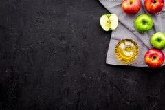 Ελαφριά σάλτσα σαλάτας Ξίδι μηλίτη της Apple στο μπουκάλι μεταξύ των φρέσκων μήλων στο μαύρο διάστημα αντιγράφων άποψης υποβάθρου Στοκ Φωτογραφίες