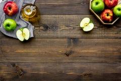 Ελαφριά σάλτσα σαλάτας Ξίδι μηλίτη της Apple στο μπουκάλι μεταξύ των φρέσκων μήλων στο σκοτεινό ξύλινο διάστημα αντιγράφων άποψης Στοκ Φωτογραφίες