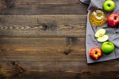 Ελαφριά σάλτσα σαλάτας Ξίδι μηλίτη της Apple στο μπουκάλι μεταξύ των φρέσκων μήλων στο σκοτεινό ξύλινο διάστημα αντιγράφων άποψης Στοκ Εικόνες