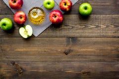 Ελαφριά σάλτσα σαλάτας Ξίδι μηλίτη της Apple στο μπουκάλι μεταξύ των φρέσκων μήλων στο σκοτεινό ξύλινο διάστημα αντιγράφων άποψης Στοκ εικόνα με δικαίωμα ελεύθερης χρήσης